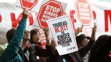 Demonstrators protest the proposed Kinder Morgan pipeline while Prime Minister Justin Trudeau arrives at HMCS Discovery in Vancouver on Tuesday. (BEN NELMS/REUTERS)