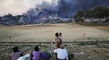 Smoke rises as people look on in Meikhtila on March 21, 2013, when 25 Muslims were killed in a massacre led by Buddhist monks. (Soe Zeya Tun/REUTERS)
