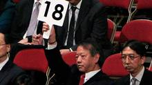 A representative of unlisted developer Chinachem raises his paddle for a bid during a land auction in Hong Kong October 12, 2010. (TYRONE SIU)