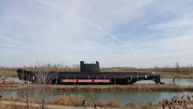 HMCS Ojibwa, the last of Canada's Oberon-class, Cold War era submarines, makes its way through the Welland Canal system in St. Catharines, Ont., on Sunday. Thousands of people came out to watch the unusual event.  Ojibwa was given a million-dollar makeover in Hamilton, before embarking on its journey to The Elgin Military Museum in Port Burwell, Ont., on Lake Erie. (Glenn Lowson for The Globe and Mail)