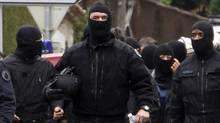 Masked French special unit policemen leave after the assault to capture gunman Mohamed Merah during a raid on a five-storey building in Toulouse (JEAN-PAUL PELISSIER/Jean-Paul Pelissier/Reuters)