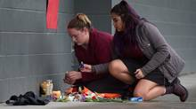 Young women place candles at a memorial for a female student who died after being stabbed at Abbotsford Senior Secondary School, on Nov. 2, 2016. (DARRYL DYCK/THE GLOBE AND MAIL)