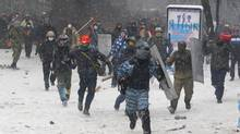 A police officer runs away during clashes with protesters in central Kiev, Jan. 22, 2014. Two protesters whose bodies were found Wednesday near the site of clashes with police were shot with live ammunition, prosecutors said Wednesday, raising fears that their deaths — the first after two months of largely peaceful protests — could further fuel violence on the streets of the Ukrainian capital. (Sergei Grits/AP)