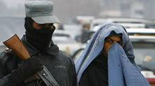 An Afghan policeman keeps watch as a woman pass by a check point in Kabul February 26, 2012. Afghanistan's interior ministry said on Sunday it suspects one of its employees may have killed two U.S. officers inside the ministry a day earlier, an attack that prompted NATO to recall all its staff from ministries. (OMAR SOBHANI/REUTERS/OMAR SOBHANI/REUTERS)