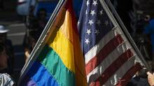 A rainbow flag which represents the LGBT community, and a U.S. flag are displayed together on the steps of the Sacramento LGBT Community Center in Sacramento, Calif., on Friday, June 26, 2015. Same-sex couples won the right to marry nationwide Friday as a divided Supreme Court handed a crowning victory to the gay rights movement, setting off a jubilant cascade of long-delayed weddings in states where they had been forbidden. (Randall Benton/AP)