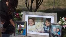 Family friend Nissy Koye, left, places flowers beside photographs of late brothers Alan and Ghalib Kurdi and their mother Rehanna displayed outside the home of their aunt Tima Kurdi, in Coquitlam, B.C., on Friday, September 4, 2015. Two alleged people-smugglers are on trial in Turkey accused of causing the death of 3-year-old Syrian migrant boy Alan Kurdi and four other people. (DARRYL DYCK/THE CANADIAN PRESS)