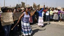 Women protest against the police near the scene of the shooting at the Lonmin mine on Friday, Aug. 17, 2012. (THEMBA HADEBE/AP)