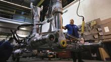 A worker works on landing gear without wheels at the Héroux-Devtek plant in Quebec, in this file photo. (Héroux-Devtek)