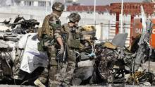 French soldiers arrive at the scene of a suicide bombing, Tuesday, Sept. 18, 2012 in Kabul, Afghanistan. A suicide bomber rammed a car packed with explosives into a mini-bus carrying foreign aviation workers to the airport in the Afghan capital early Tuesday, killing at least nine people in an attack a militant group said was revenge for an anti-Islam film that ridicules the Prophet Muhammad (Ahmad Jamshid/The Associated Press)