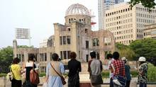 Visitors stand and watch in front of the Atomic Bomb Dome as they hear story about the atomic bombing from a guide at the Hiroshima Peace Memorial Park in Hiroshima, western Japan Monday, Aug. 4, 2008. (Katsumi Kasahara / AP/Katsumi Kasahara / AP)