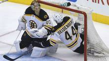 Boston Bruins Dennis Seidenberg slides into his own net as Bruins goaltender Tuuka Rask  looks on during second period of game six NHL eastern conference playoff May 12, 2013. (Moe Doiron/The Globe and Mail)