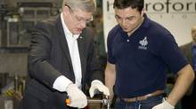 Prime Minister Stephen Harper receives instruction from worker Robert Muraca as they tour a factory during a campaign visit to a factory in Brampton, March 30, 2011. (Kevin Van Paassen/The Globe and Mail/Kevin Van Paassen/The Globe and Mail)