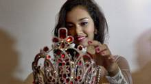 May Myat Noe, Myanmar's first international beauty queen, winner of 2014 Miss Asia Pacific World adjusts $ 100,000 worth crown that she allegedly ran away with, during a press conference in Yangon, Myanmar Tuesday, Sept 2, 2014. Dethroned beauty queen from Myanmar says she won't return her $100,000 crown until the pageant's organizers apologize for calling her a liar and a thief. (Gemunu Amarasinghe/AP)
