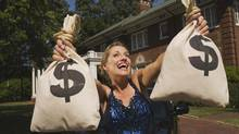 Rich woman with money bags in front of mansion. (Jupiterimages/Photos.com)