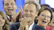 Prime Minister Donald Tusk, center, celebrates with Health Minister Ewa Kopacz, right, and Foreign Minister Radek Sikorski, background left, as the first exit poll is published during the election party of Tusk's Civic Platform, a centrist and pro-EU party, in Warsaw Sundey, Oct. 9, 2011. (AP/ALIK KEPLICZ/AP/ALIK KEPLICZ)