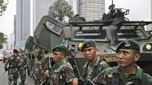 Indonesian soldiers stand guard near the site where an explosion went off in Jakarta, Indonesia Thursday, Jan. 14, 2016. Attackers set off explosions at a Starbucks cafe in a bustling shopping area of downtown Jakarta and waged gun-battles with police Thursday, leaving bodies in the streets as office workers watched in terror from high-rise windows. (Dita Alangkara/AP)