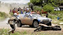 Donald Hatton runs to pick up his KTM motorcycle after a fall during the 2010 Dakar Rally. (JACKY NAEGELEN/REUTERS)