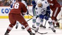 Vancouver Canucks' Zack Kassian (9) passes the puck past Phoenix Coyotes' Michael Stone (26) during the first period of an NHL hockey game on Tuesday, March 4 in Glendale, Ariz. (Ross D. Franklin/AP)