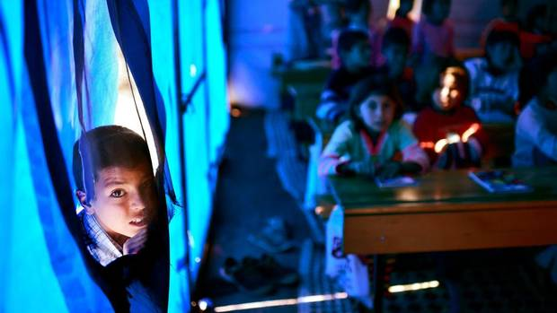 "A Syrian Kurdish boy peers as children take lessons in a makeshift school tent in a refugee camp in the town of Suruc, Sanliurfa province. Turkey's maintained an ""open door"" policy for all those fleeing Syria's civil war and there are now over 1.5 million Syrian refugees living in the country. (Aris Messinis/AFP/Getty Images)"