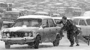 Two young men help push a Lada Zhiguli car away from a busy and icy thoroughfare in downtown Moscow. Friday, March 18, 1994.
