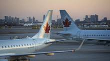An Air Canada jet heads to arrival gates as another sits waiting at another gate at Pearson International Airport. (Fred Lum/The Globe and Mail)