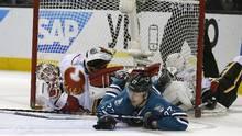 San Jose Sharks right wing Joonas Donskoi (27) collides with Calgary Flames goalie Karri Ramo during the third period of an NHL hockey game in San Jose, Calif., Feb. 11, 2016. (Tony Avelar/AP)