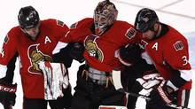 Ottawa Senators goalie Craig Anderson (C) is helped off the ice by teammates Chris Phillips (L) and Marc Methot after getting injured during the third period of their NHL hockey game against the New York Rangers in Ottawa February 21, 2013 (Reuters)