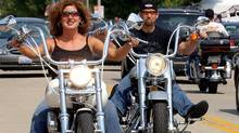 Theresa and Scott Crowell of Charlotte, N.C., ride their Harleys down Main Street in Thiensville, Wis., in this file photo. Harley-Davidson is ramping up its attempts to market to women and ethnic minorities. (STEPHAN SAVOIA/AP)