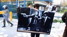 TEHRAN, IRAN - NOVEMBER 29: A man holds a poster featuring American actors John Travolta and Samuel L. Jackson in a scene from the film 'Pulp Fiction' following a break in at the British Embassy during an anti-British demonstration in the Iranian capital on November 29, 2011 in Tehran, Iran. Getty Images (Getty Images/Getty Images)