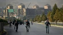Afghan security personnel walk near the site after an attack by militants that targeted the elite American University of Afghanistan, in Kabul, on Aug.25, 2016. (WAKIL KOHSAR/AFP/Getty Images)
