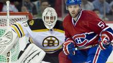 Montreal Canadiens' Mathieu Darche, right, slides in on goaltender Tim Thomas during third period Game 3 NHL playoff hockey action in Montreal, Monday, April 18, 2011. (Graham Hughes/Graham Hughes/The Canadian Press)