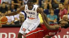 France's Alain Koffi makes contact with Canada's Jevohn Shepherd during their FIBA Basketball World Championship game in Izmir on Tuesday. (SERGIO PEREZ/Reuters)