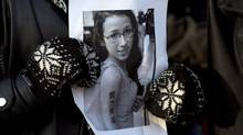 A woman holds a photo as several hundred people attend a community vigil at Victoria Park in Halifax on April 11, 2013, to remember Rehtaeh Parsons, who died by suicide. (Andrew Vaughan/The Canadian Press)