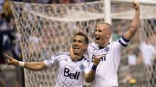 Vancouver Whitecaps FC Camilo Sanvezzo, left, celebrates his goal with teammate Kenny Miller during the first half against Chivas USA during first half of MLS soccer action in Vancouver, Wednesday, June, 19, 2013 (The Canadian Press)