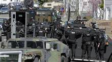 Tactical teams drive through a neighborhood while searching for a suspect in the Boston Marathon bombings in Watertown, Mass., on April 19, 2013. (Charles Krupa/Associated Press)
