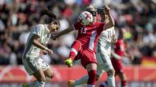 Germany's Hasret Kayikci and Canada's Sophie Schmidt challenge for the ball during a soccer match between Germany and Canada in the Steigerwald stadium in Erfurt, Germany, on April 9, 2017. (Thomas Eisenhuth/AP)