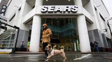 A woman walks her dog past the Sears store in downtown Vancouver, B.C., on Friday March 2, 2012. The store was among those earmarked to be closed by the retailer. (DARRYL DYCK/THE CANADIAN PRESS)