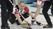 Canada's skip Jacobs Brad delivers a stone during their men's curling round robin game against the U.S. in the Ice Cube Curling Centre at the Sochi 2014 Winter Olympic Games February 16, 2014. (INTS KALNINS/REUTERS)