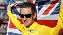 Sky Procycling rider and leader's yellow jersey Bradley Wiggins of Britain holds a British national flag as he celebrates his overall victory on the Champs Elysees after the final 20th stage of the 99th Tour de France cycling race between Rambouillet and Paris, July 22, 2012. Wiggins became the first Briton to win the Tour de France when he claimed the 99th edition of the greatest cycling race on Sunday. (CHARLES PLATIAU/REUTERS)