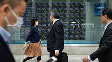 Pedestrians walk in front of a quotation board flashing the Nikkei key index of the Tokyo Stock Exchange in Tokyo, on April 18, 2017. (KAZUHIRO NOGI/AFP/Getty Images)
