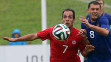 Canada's Randy Pedro Pacheco, left, challenges for the ball with Alexandru Gatcan of Moldova during a friendly soccer match between Moldova and Canada in Amstetten Mauer, Austria, Tuesday, May 27, 2014. (Associated Press)