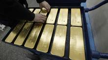 A worker places ingots of 99.99 per cent pure gold at the Krastsvetmet nonferrous metals plant in Russia's Siberian city of Krasnoyarsk on April 12, 2012. (ILYA NAYMUSHIN/REUTERS)