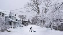 A man clears snow from the middle of the street during a snow storm in Halifax on Jan. 13, 2016. (Darren Calabrese/THE CANADIAN PRESS)