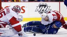 Vancouver Canucks' David Booth is knocked to the ice by Detroit Red Wings' Niklas Kronwall while trying to score on Red Wings goaltender Jimmy Howard during the first period of their game in Vancouver on Feb. 2, 2012. (Ben Nelms/Reuters/Ben Nelms/Reuters)