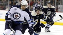 Winnipeg Jets' Evander Kane (L) fights for the puck with Columbus Blue Jackets' Grant Clitsome during the first period of their NHL hockey game in Columbus, Ohio November 12, 2011. (MATT SULLIVAN/Reuters)