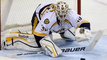 Nashville Predators' goaltender Carter Hutton (30) covers a bouncing puck during third period NHL action in Winnipeg, Sunday, October 20, 2013. (Trevor Hagan/THE CANADIAN PRESS)