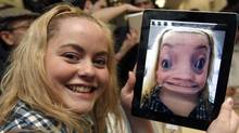 Rebecca Felix poses with an Apple iPad 2, showing a distorted image of herself at the Apple store in London March 25, 2011.