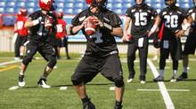 Calgary Stampeders' quarterback Drew Tate, left, takes part in a drill as his teammates look on during the first day of training camp in Calgary, Alta., Sunday, June 1, 2014. (Jeff McIntosh/THE CANADIAN PRESS)