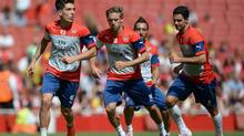 Arsenal's Hector Bellerin, left, Nacho Monreal and Mikel Arteta, right, in action, during a training session, at the Emirates Stadium, London, Thursday Aug. 7, 2014. (Andrew Matthews/AP)