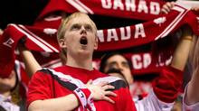 A Canadian fan sings the national anthem before a women's soccer game in Vancouver. (DARRYL DYCK/THE CANADIAN PRESS)
